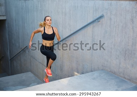 Athletic woman running up stairs during cardio - interval training - stock photo