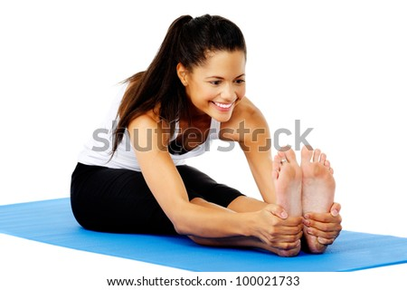 Athletic woman smiling while she stretches forward, Part of a collection of yoga poses by a fit active hispanic woman; sit-up pose - stock photo
