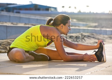 Athletic woman stretching her hamstrings on a beach during a training run on a warm, summer evening. - stock photo