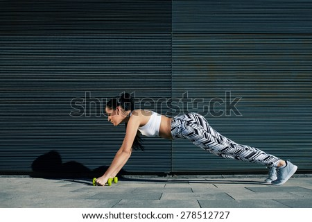 Athletic woman with perfect figure and buttocks shape doing press ups with dumbbells near copy space wall for your text message, fit female in workout gear doing push-ups on black background outdoors - stock photo