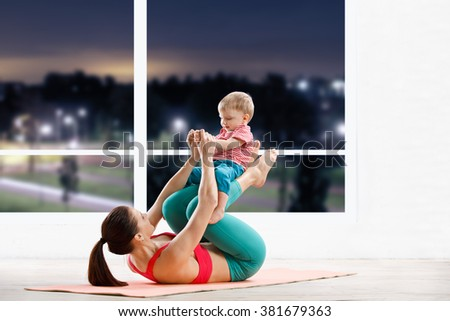 athletic woman working out with little baby at fitness class in evening - stock photo