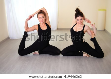 athletic women dressed in beautiful sportswear doing yoga pose, sitting on the floor. Training in the lit gym. - stock photo