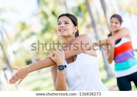 Athletic women stretching her arms at the park - stock photo