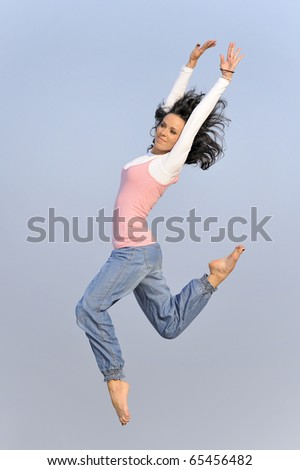 athletic young girl jumping on the beach in the Baltic Sea - stock photo