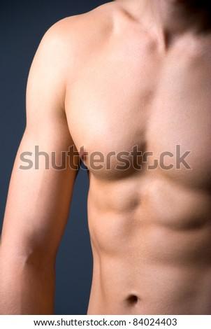 Athletic young male's torso. Dark background, studio shot - stock photo