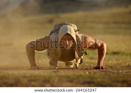 athletic young man exercising outdoor on dusty field - stock photo