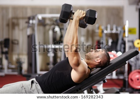 Athletic young man laid on back working his chest with heavy dumbbells - stock photo