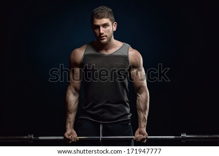 athletic young man lifting weights - stock photo