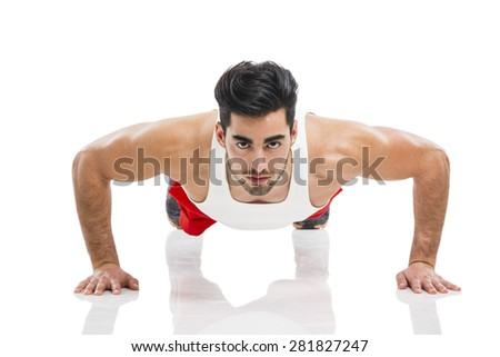 Athletic young man making push-up, isolated over a white background - stock photo