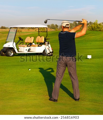 Athletic young man playing golf, golfer hitting fairway shot, swinging club - stock photo