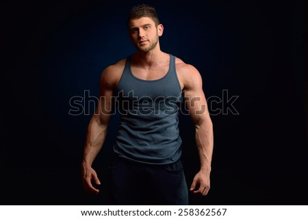 athletic young man portrait in studio with dark background - stock photo