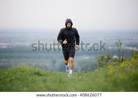 Athletic young man running during autumn, winter morning. Healthy lifestyle - stock photo