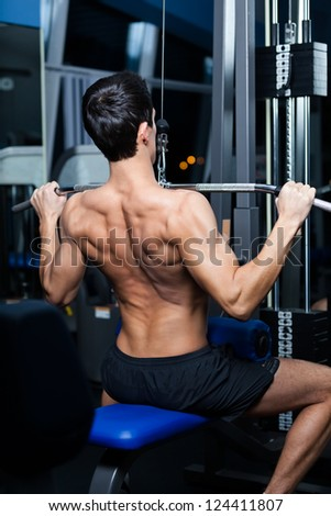 Athletic young man works out on simulator in fitness gym - stock photo