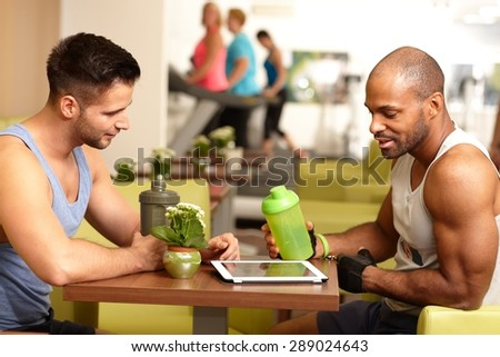 Athletic young men sitting at table in gym, taking a break, drinking refreshment, using tablet computer. - stock photo