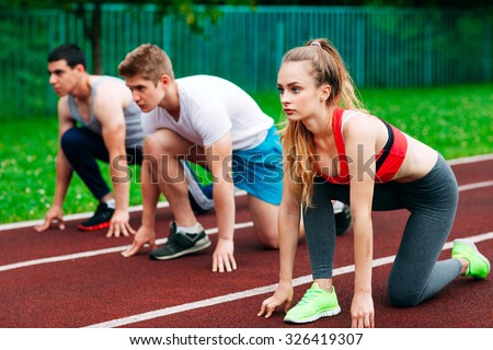 Athletic young people on track starting to run. Healthy fitness concept with active lifestyle. - stock photo