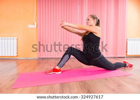 Athletic Young Woman in a Deep Lunge Stretch with Arms Forward on Top of a Fitness Mat Inside the Studio. - stock photo