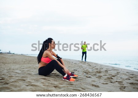 Athletic young woman in sportswear resting on the beach after exercise and looking at landscape, fitness man running along the beach looking at girl, sport people and active lifestyle - stock photo