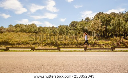 Athletic young woman in sportswear running on a runway outdoors. Healthy lifestyle concept. - stock photo