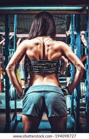 Athletic young woman showing muscles of the back - stock photo