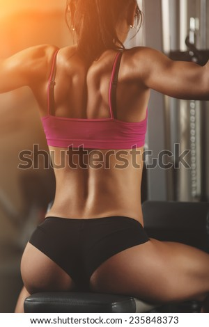 Athletic young woman showing muscles of the back and hand. Athletic young woman doing a fitness workout - stock photo