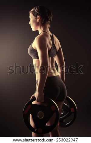 Athletic young woman stands with barbell plates. Fitness sports. Healthcare, bodycare. - stock photo