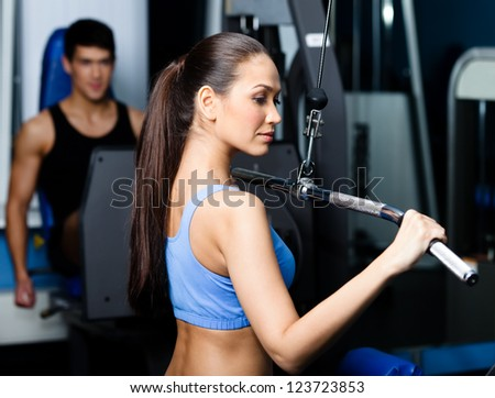 Athletic young woman works out on training apparatus in gym class - stock photo