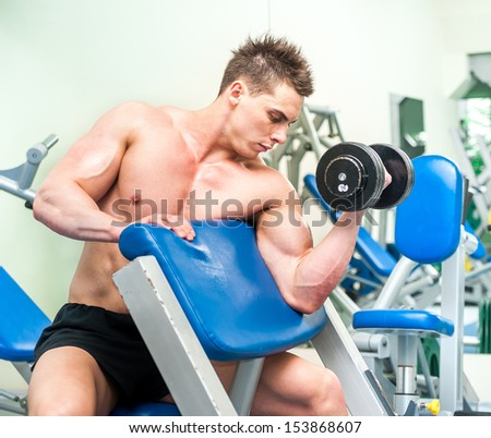 athletically built sportsman doing exercises with dumbbells for the biceps in the gym - stock photo