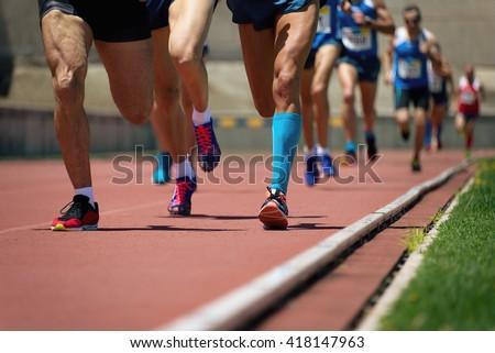 Athletics people running on the track field - stock photo