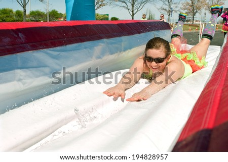 ATLANTA, GA - APRIL 5:  A young woman dives onto a wet plastic slide as she makes her way through the obstacles at the Ridiculous Obstacle Challenge (ROC) 5K race, on April 5, 2014 in Atlanta, GA.  - stock photo
