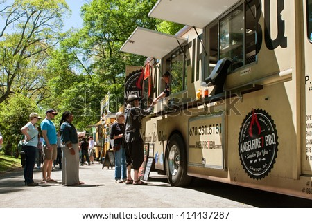 ATLANTA, GA - APRIL 16:  People stand in line to buy meals from a food truck lined up in Grant Park at the Food-o-rama festival on April 16, 2016 in Atlanta, GA.  - stock photo