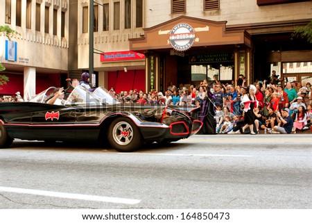 ATLANTA, GA - AUGUST 31:  Batman rides in the batmobile down Peachtree Street in the annual Dragon Con parade on August 31, 2013 in Atlanta, GA.  - stock photo