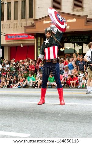 ATLANTA, GA - AUGUST 31:  Super hero Captain America raises his shield to salute the crowd at the annual Dragon Con parade on Peachtree Street, on August 31, 2013 in Atlanta, GA.   - stock photo