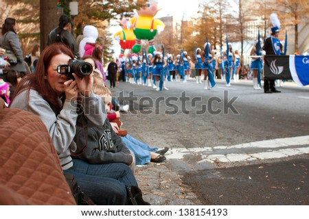 ATLANTA, GA - DECEMBER 1:  Spectators watch from the curb as the Atlanta Christmas parade takes place on Peachtree Street on December 1, 2012 in Atlanta, GA. Thousands of spectators attended. - stock photo