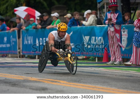 ATLANTA, GA - JULY 4:  An athlete competing in the wheelchair portion of the Peachtree Road Race speeds toward the finish line in the annual Atlanta event, on July 4, 2015 in Atlanta, GA.    - stock photo