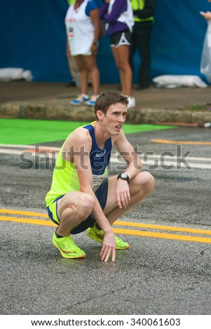 ATLANTA, GA - JULY 4:  An exhausted male runner kneels to catch his breath after crossing the finish line at the 46th running of the Peachtree Road Race 10K on July 4, 2015 in Atlanta, GA.  - stock photo