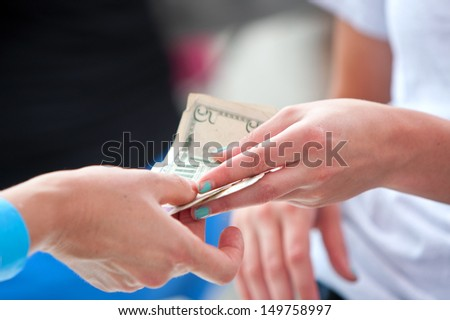 ATLANTA, GA - JULY 27:  Closeup of two women's hands exchanging money at a vendor booth at the 3rd Annual Atlanta Ice Cream Festival in Piedmont Park, on July 27, 2013 in Atlanta.    - stock photo