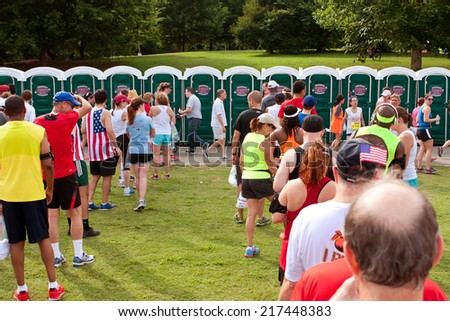 ATLANTA, GA - JULY 4:  Exhausted runners wait in long lines to use a Johnny On The Spot portable toilet, after just completing the Peachtree Road Race 10K on July 4, 2014 in Atlanta, GA.   - stock photo