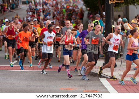 ATLANTA, GA - JULY 4: Thousands of runners run down Peachtree Street on their way to the finish line of the Peachtree Road Race on July 4, 2014 in Atlanta, GA.  - stock photo