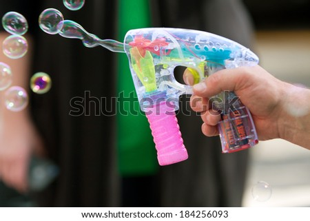 ATLANTA, GA - MARCH 15:  A man's hand uses a bubble gun to blow bubbles at the St. Patrick's Day parade on Peachtree Street, on March 15, 2014 in Atlanta, GA.  - stock photo