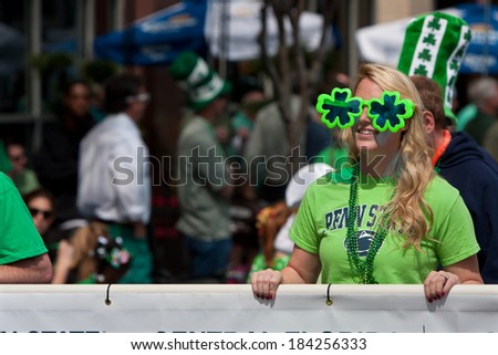 ATLANTA, GA - MARCH 15:  A woman wearing shamrock sunglasses carries a banner down Peachtree Street as part of the St. Patrick's parade, on March 15, 2014 in Atlanta, GA.   - stock photo