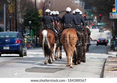 ATLANTA, GA - MARCH 15:  The Atlanta police calvary patrols an area along Peachtree Street shortly before the start of the annual St. Patrick's Day parade, on March 15, 2014 in Atlanta, GA.   - stock photo
