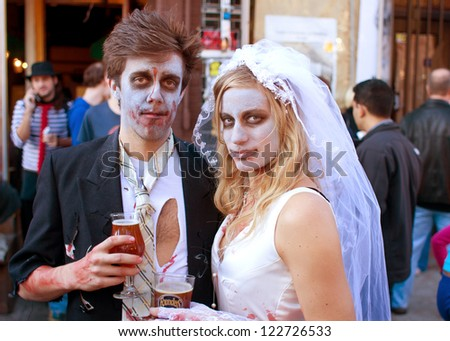 ATLANTA, GA - OCTOBER 20:  An unidentified couple dressed like a zombie bride and groom, enjoy a cold beer after walking in the Little Five Points Halloween parade on October 20, 2012 in Atlanta. - stock photo