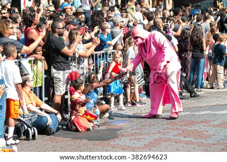 ATLANTA, GA - SEPTEMBER 5:  A person dressed as a pink Darth Vader character interacts with spectators along the parade route of the annual Dragon Con Parade on September 5, 2015 in Atlanta, GA.  - stock photo