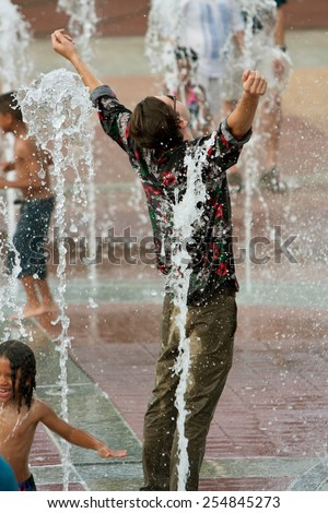 ATLANTA, GA - SEPTEMBER 6:  A young man poses triumphantly while getting soaked wearing street clothes standing in the fountain at Centennial Park on September 6, 2014 in Atlanta, GA.  - stock photo