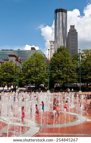 ATLANTA, GA - SEPTEMBER 6: Kids get wet playing in the fountain at Centennial Park on a hot summer day on September 6, 2014 in Atlanta, GA.  - stock photo