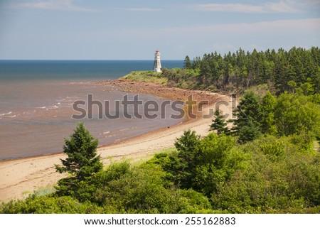 Atlantic beach coast with Cape Jourimain lighthouse, New Brunswick, Canada - stock photo
