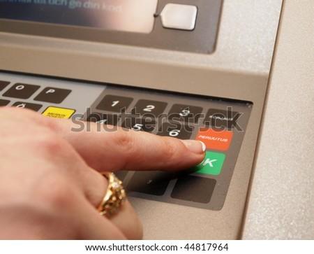 ATM dials - someone pressing green OK button - stock photo