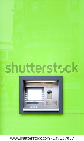 ATM or cash machine in green wall shining in sun with weak reflection of building and people. Fast and convenient way of cash-out and payments. Bank operations with accounts using plastic card. - stock photo