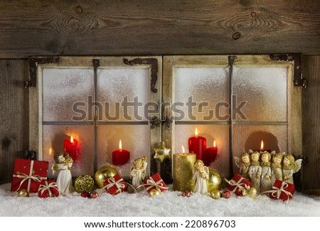 Atmospheric and romantic classical christmas window decoration with red candles, snow and wood in white, red and golden colors. - stock photo