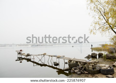Atmospheric misty landscape with the river and the bridge across the Dnieper. Homemade bridges for fishing. Calm, meditation and balance - stock photo